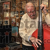 The soothing sounds of red metal: Chuck Shutt plucks the strings on his red metal bass at his home Friday, Nov. 21. Shutt found the bass at an antique shop in the 1960s.
