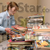 A place for everything: Rachel Gutish stacks books for middle schoolers in the proper place as she and several other Brownies and Junior Brownies help organize donated books that will be included in Christmas baskets.