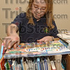 Organizer: Junior Brownie Grace Collins sorts through donated books at the Tribune-Star Thursday afternoon. She and fellow Brownies organized hundreds of books that will be distributed with the Tribune-Star's Christmas baskets.