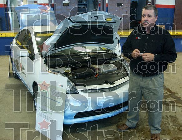 Plug it in: Rick Burger of Duke Energy strands by the Toyota Prius his company has bought. On Monday he touted the 2-4 cents per mile he pays to operate the vehicle and the green apsect of owning and driving one.