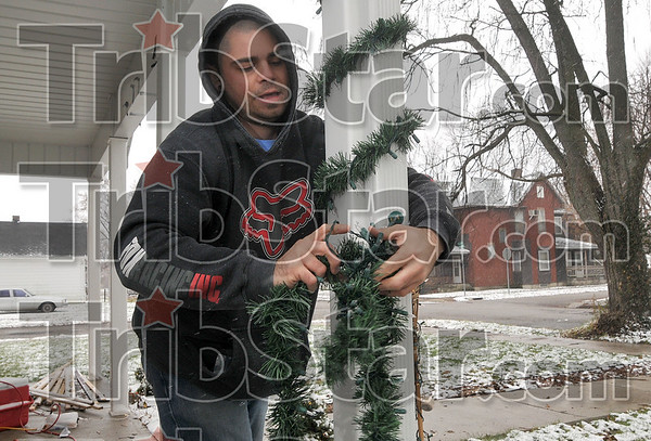 13 1/2 Street resident and Indiana State University student Clay Schapker, 27, decorates his home with a garland and light combination as he withstands the cold wind and snow flakes Monday.
