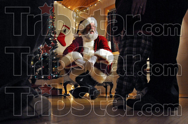 Coaxing: Santa Claus sits in his house in Deming Park Monday evening during the judging of the annual Christmas in the Park and attempts to coax a three-year-old onto his lap. Santa is provided by the Terre Haute Parks Department for the event.