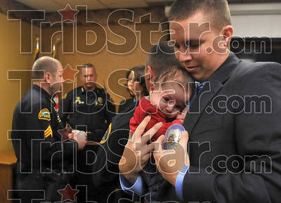 Daddy's new badge: New Terre Haute Police Department officer Justin Sears positions his new daughter, two-month-old Alyssa Marie, and his new patrolman badge for a photo for his wife, Jennifer Sears, Monday at police headquarters.