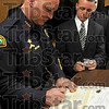 It's official: Terre Haute Police Chief John Plasse signs paperwork for new Terre Haute Police patrolman Devon Huebner after a swearing in ceremony Monday.