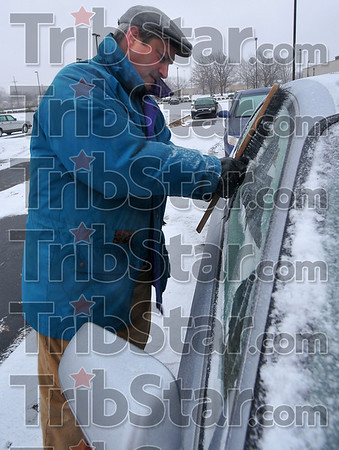 Iced over: Mike Chambers scrapes the windows of his car after a day inside at Indiana State University.