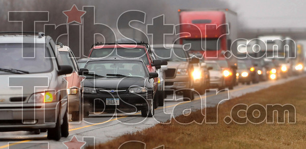 Interstate slowdown: A motorist with Iowa license plates, third from left, sits in line with other drivers as they wait for emergency/rescue personnel to clear the eastbound lane of I-70 Tuesday between the US 41 and US 46 exits after an accident.