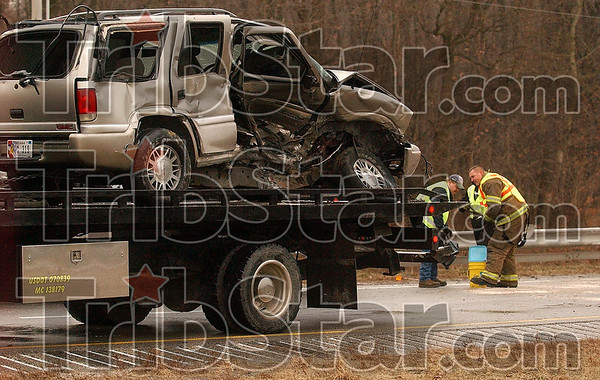 Icey danger: A towing service employee and a member of the Terre Haute Fire Department clean up remnants of a crash that occurred on I-70 Tuesday near the 10-mile marker in the eastbound lane.