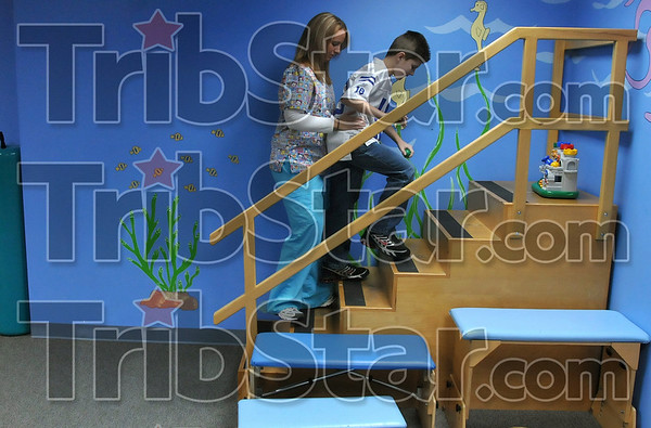 Facing his uphill climb: Ten-year-old Cameron Switzer works on climbing stairs with physical therapist Erin Ford Tuesday morning at Union Hospital Pediatric Therapy.