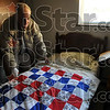 A little warmer at night: William Ross, a resident of The Heritage, a military nursing home in Hutsonville, Ill., spreads his new quilt on his bed at the facility Tuesday. Ross received the quilt in a package from inmates in the P.L.U.S. unit at the Wabash Valley Correctional Facility near Carlisle.