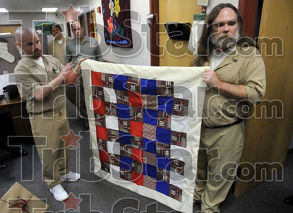 For those that served: Wabash Valley Correctional Facility inmates in the P.L.U.S. unit Randy O'Brien and Kevin Henry display one of the quilts made by the unit for veterans Tuesday at the facility near Carlisle.