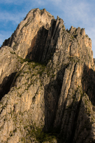 The massive walls of El Potrero Chico rise magnificently above the canyon floor in the evening light.