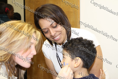 Meghan O'Connor of YAP, paints three-year-old Xavier's face while mom Rose supervises during the City of Newburgh Christmas Extravaganza held at the Business Resource Center on December 12, 2008.