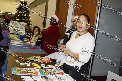 Jessica Perez hands out information at the Fidelis Care table at the City of Newburgh Christmas Extravaganza held at the Business Resource Center on December 12, 2008.