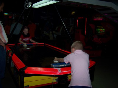 Noah and Clark playing air hockey at the arcade