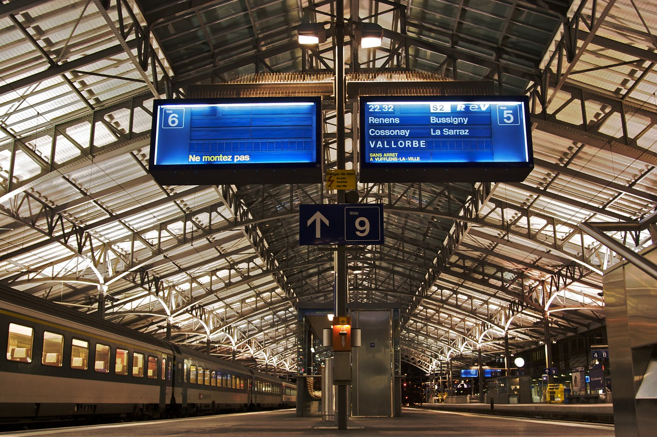 Fairly late at night in Lausanne railway station, with a well-lit vaulted roof. The train due on platform 5 (on the right of this picture) is a local service for several suburbs of Lausanne and close regional locations.