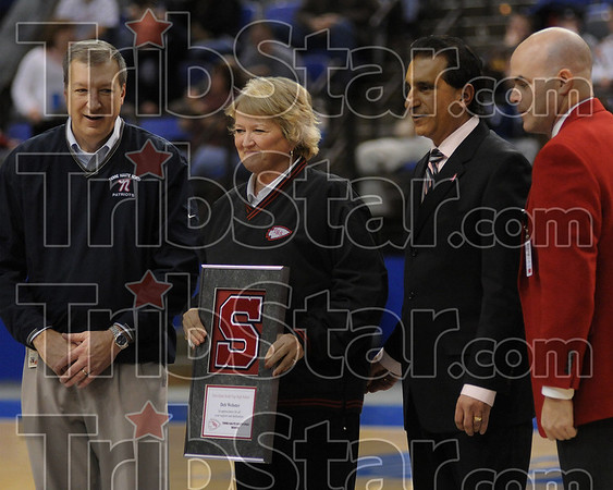 Terre Haute South Athletic Director Deb Webster is presented a plaque for her many years of service during the North-South game Friday at Hulman Center. Standing with Webster is Terre Haute North Principal Mick Newport, Superintendent Dan Tanoos and South Principal Troy Fears.