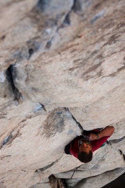 Evening sun casts a shadow over Kelsey as he works his way up <i>Sail Away 5.8</i> in Joshua Tree NP.