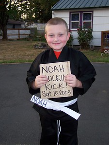 Noah earned his white belt by breaking the wooden board he's holding