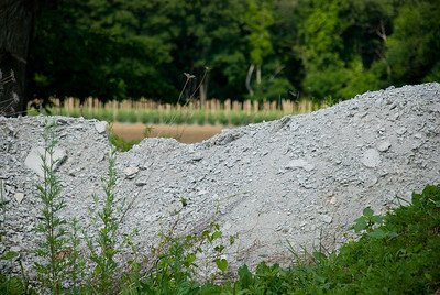 A mound of light gray gravel/rock/dust with a field in the background.