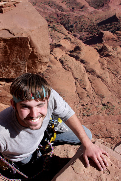Richard grins through the exposure on the last few moves of the <i>Kor-Ingalls Route 5.9</i> with hundreds of feet of vertical below.