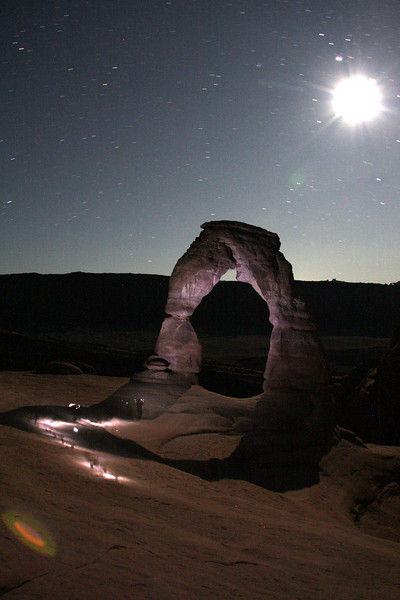 Delicate Arch stands silent in the night, as Kelsey moves closer with his headlamp to examine the awe-inspiring feature up close.