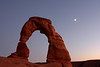 A distant moon sheds some light on the backside of Delicate Arch after the sun has gone down.