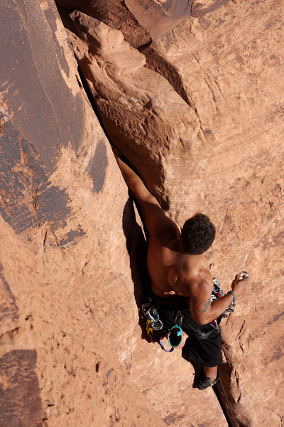 Kelsey places pieces in a deep flaring crack as he climbs higher.