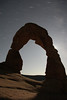 Stars whiz by as Delicate Arch stands in the monlight.