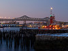 Tugboats and the the Tobin Bridge from East Boston at twilight.