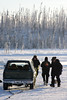 A bomb squad member supervises the placing of the explosives in the ice around the vehicle.