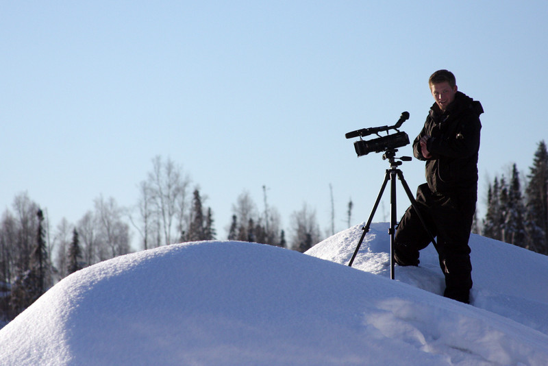 A crew member films from atop a snowbank overlooking the lake.
