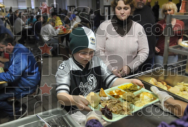 """""""I want to help people"""": Nine-year-old Kolby Fieck of Riley picks up a tray of Thanksgiving dinner to serve to one of the residents of the Lighthouse Mission Thursday as his mom, Stefanie Fieck, looks on."""