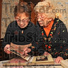 History: Rose Ann Brody and Evelyn Giffel look over scrapbooks from years gone by that chronicle the activities of the Women's Department Club.