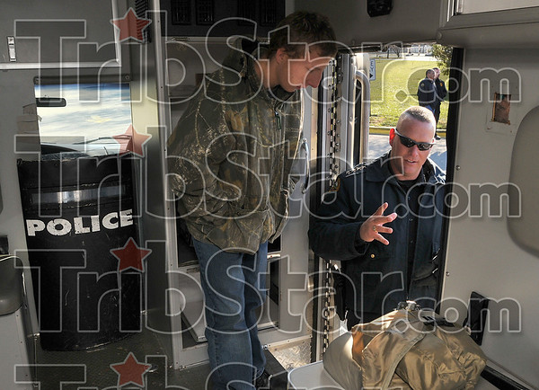 Tools of the trade: Terre Haute North junior Victor Price, 16, listens as Police Chief John Plasse describes how some of the tools work in the department's new special response team vehicle Friday at the school.