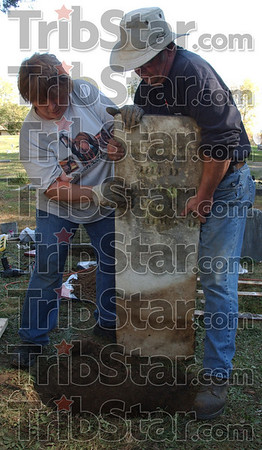Back in place: Kyle Ellis and her husband Mike reset one of he grave markers in Hixon cemetary. The couple along with several other volunteers have spent well over 100 man hours restoring the Parke county cemetary.