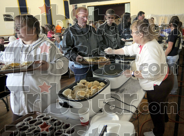 Food line: Volunteers serve food at the Hillcrest Community Center in Clinton Saturday afternoon.