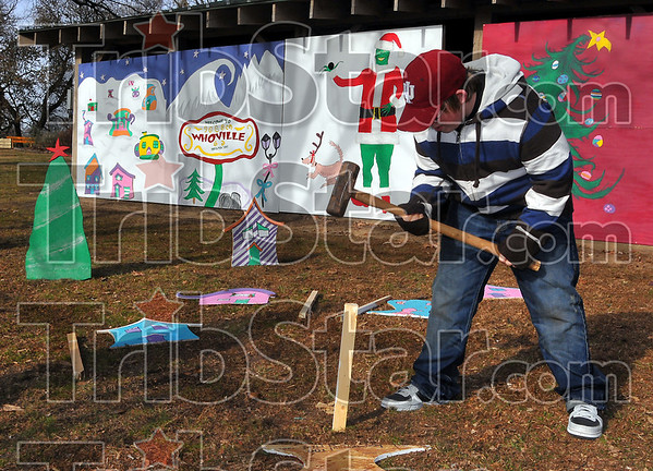 Support staff: A.J. Maners pounds in a stake that will support part of the decorations being placed at the Terre Haute South Vigo High School Christmas display at Deming Park. The effort is part of Terre Haute First National Bank's annual Christmas in the Park celebration.