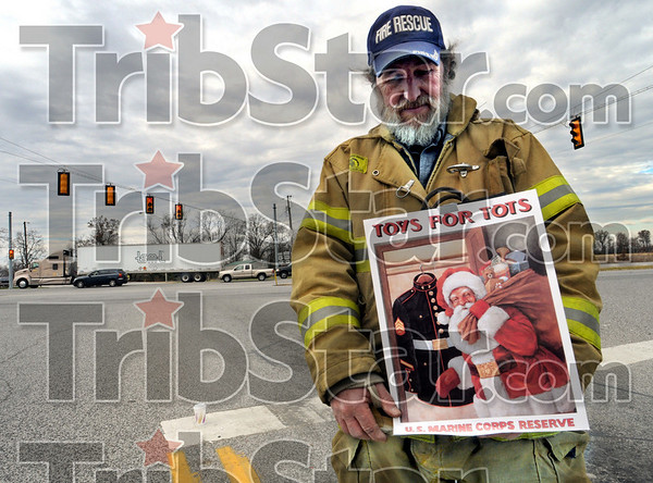 Santa's helper: Shelburn firefighter Earl Young looks suspiciously like the jolly character on his poster as he collects money for the Toys for Tots campaign Saturday afternoon at the intersection of US 41 and SR 48 in Sullivan County.