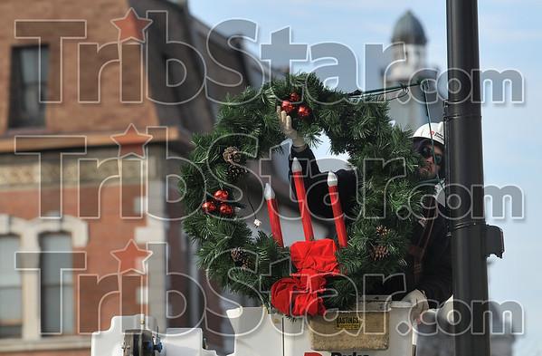 Duke Energy lineman Matt Mullenix of Brazil hangs a wreath and candle light set on a light pole on Wabash Avenue Wednesday.