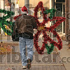 Terre Haute Chamber of Commerce President Rod Henry carries a poinsettia-shaped light set down Wabash Avenue to a light pole so a Duke Energy crew could hang it Wednesday.