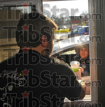 Happiness to go: Java Haute barrista Travis Beckner serves a fresh cup of coffee to Sara Yelich Wednesday afternoon.