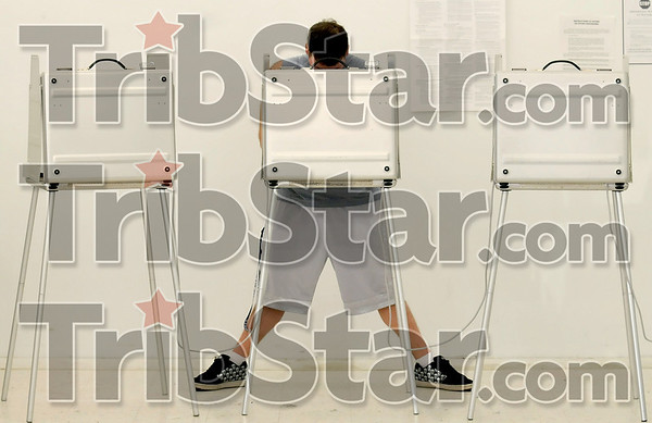 Voting symmetry: Voter Robert Hodge, Jr., 21, forms a symmetrical scene as he casts his vote Tuesday at the Plaza North poll.