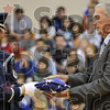 Honoring the stars and stripes: Staff Sgt. Anthony Hobson of the Indiana Air National Guard 181st Intelligence Wing Honor Guard hands a folded flag to Ind. Rep. Vern Tincher of the 46th District during the Veterans Day ceremony Monday at Honey Creek Middle School.