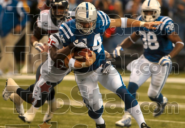 Just one more yard...: Indianapolis tight end Dallas Clark struggles for another yard or two as he is pulled down by Houston's Nick Ferguson during the Colts' win Sunday in Indianapolis.
