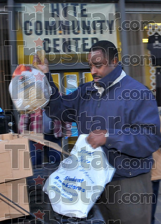 Happier holiday: Dwayne Malone loads a turkey into a plastic carrying sack Tuesday evening. The Charles T. Hyte Communnity Center distributed about 100 turkeys donated by the Paris Kroger store.