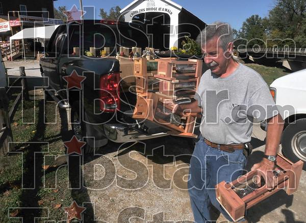 Prime real estate: Vendor Randy Marcum of New Castle unloads his bird feeders close to the Bridgeton bridge Thursday in preparation for the Covered Bridge Festival.
