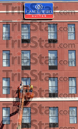 They do windows: JJ Karma employees John McVay and Paul Bugh apply caulk to the windows in the new Candlewood Suites building Thursday afternoon.