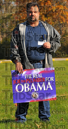 Pro Obama: Mark Swaner holds his union card as he strands with one of his union's Real Joe the Plumber yard signs.