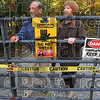 Heed the warning: After seeing neighborhood children playing in a creek that is believed to be contaminated with PCBs, Don Archambeault decided to put up warning signs that the small stream on his property is not safe. Here he and his wife, Sylinda, stand next to the locked entry gate of his property Thursday.