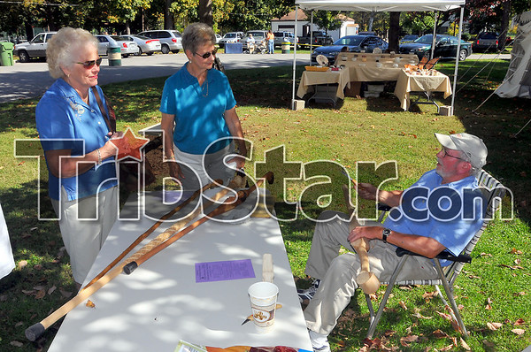 On display: John Hemminghouse talks with Barbara White and Mary K. Huber abouit his carving work at the Collett Park anniversary celebration Sunday afternoon.
